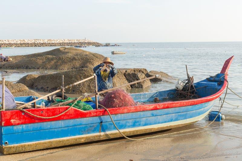 Pescador local en su barco de pesca, clasificando su captura de la mañana del cangrejo fotografía de archivo