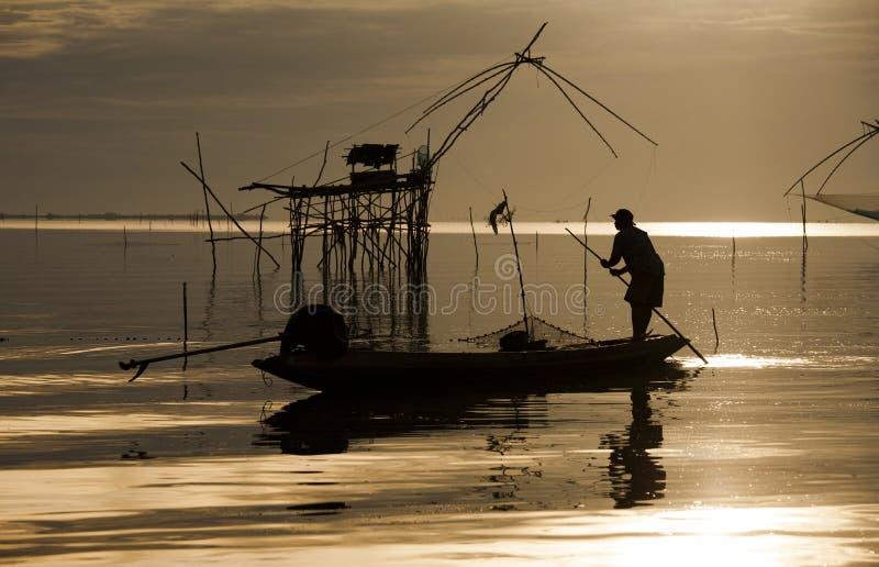 Pescador local que trabalha em seu barco no en bonito cênico do por do sol dourado imagens de stock