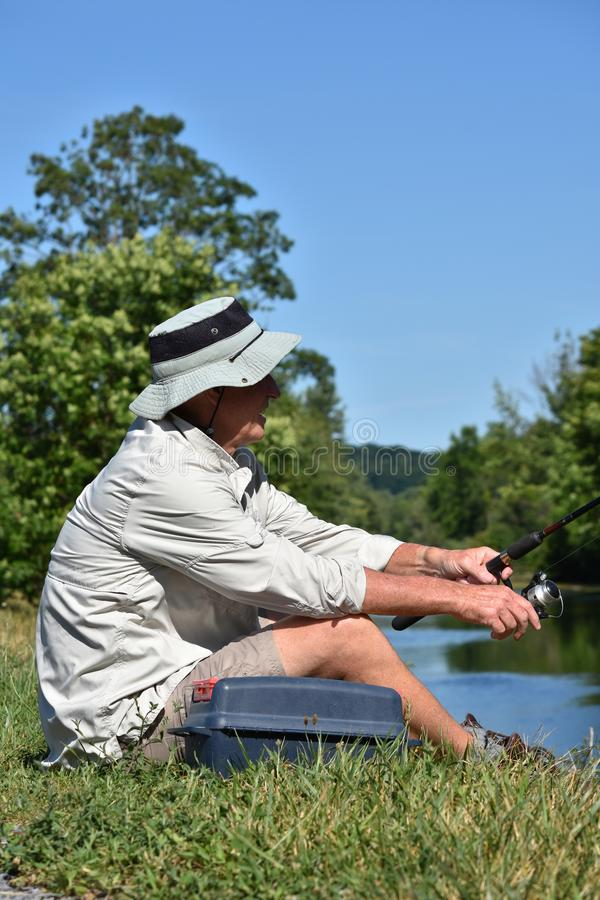 Pescador masculino Relaxing With Rod And Reel Fishing do aposentado fotografia de stock