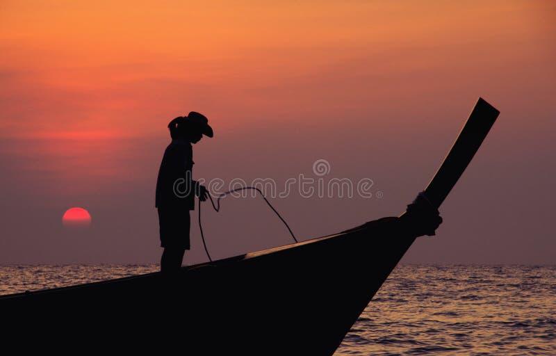 Pescador mostrado em silhueta no por do sol imagem de stock