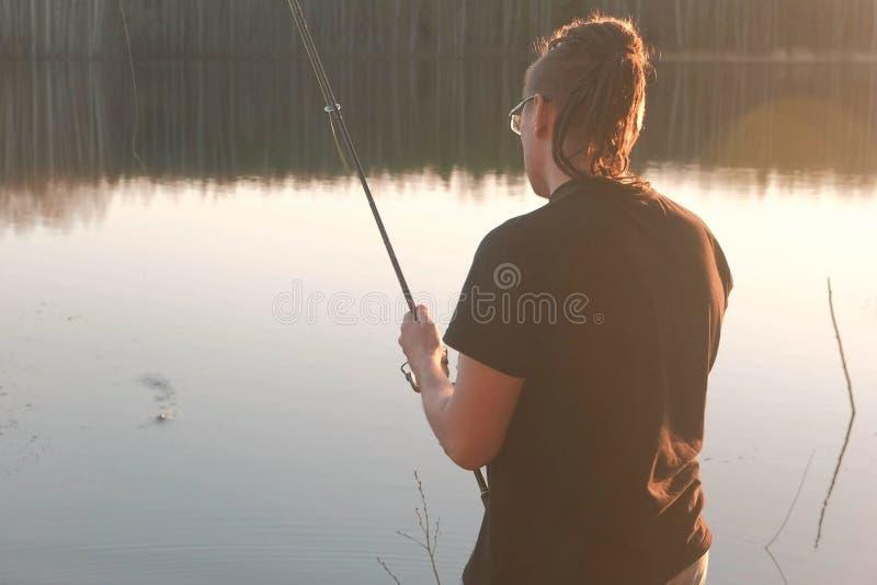 Pescador na lagoa O indivíduo novo com teme nos vidros em um peixe da pesca do t-shirt com haste foto de stock