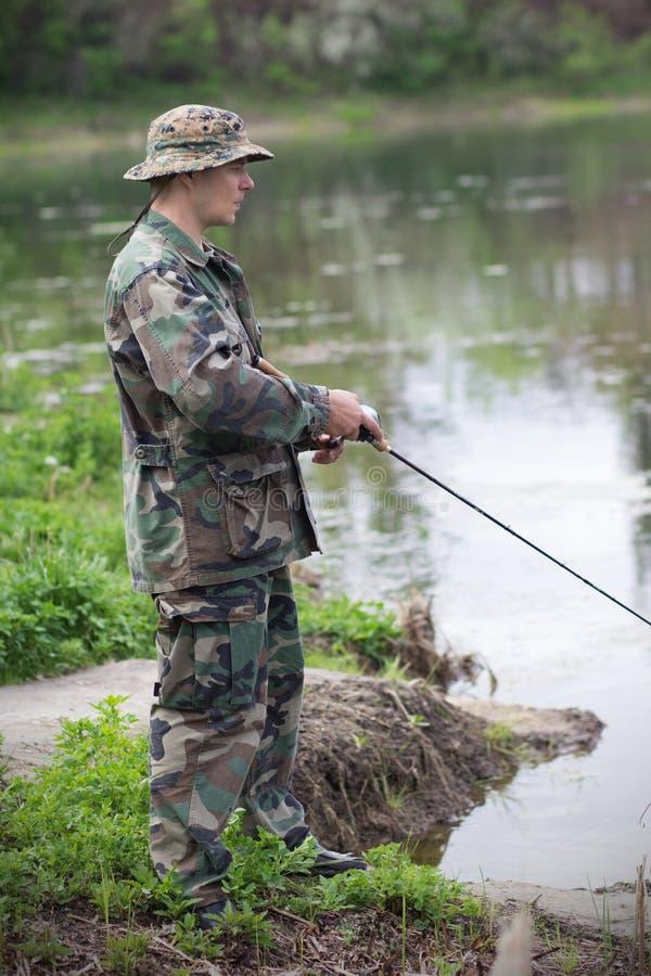 Pescador no banco de rio imagens de stock