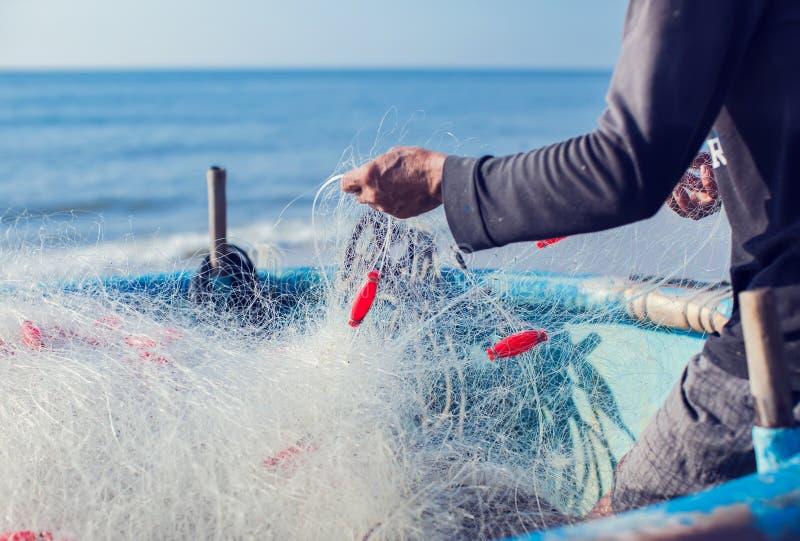 Pescador no barco com rede nas mãos foto de stock royalty free
