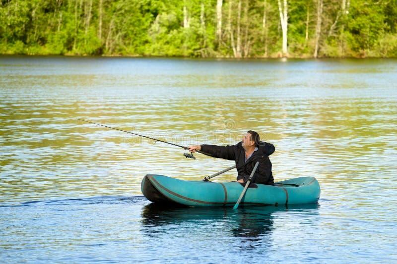 Pescador no barco de borracha foto de stock royalty free