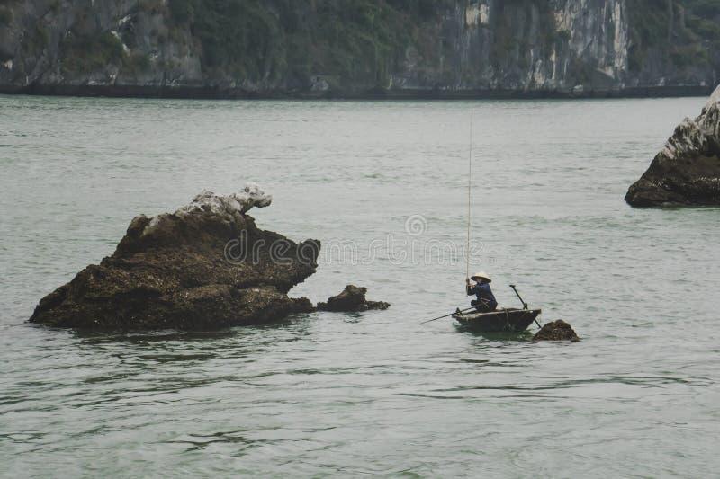 Pescador no barco longo da baía, dos peixes do Ha e na pescadora da casa na paisagem maravilhosa da baía de Halong, Vietname fotos de stock