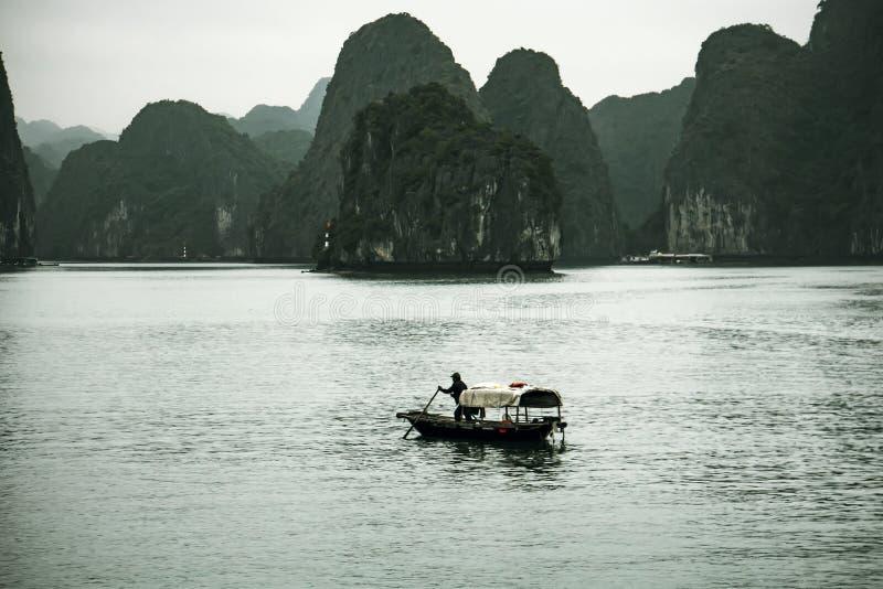 Pescador no barco longo da baía, dos peixes do Ha e nos pescadores da casa na paisagem maravilhosa da baía de Halong imagens de stock royalty free