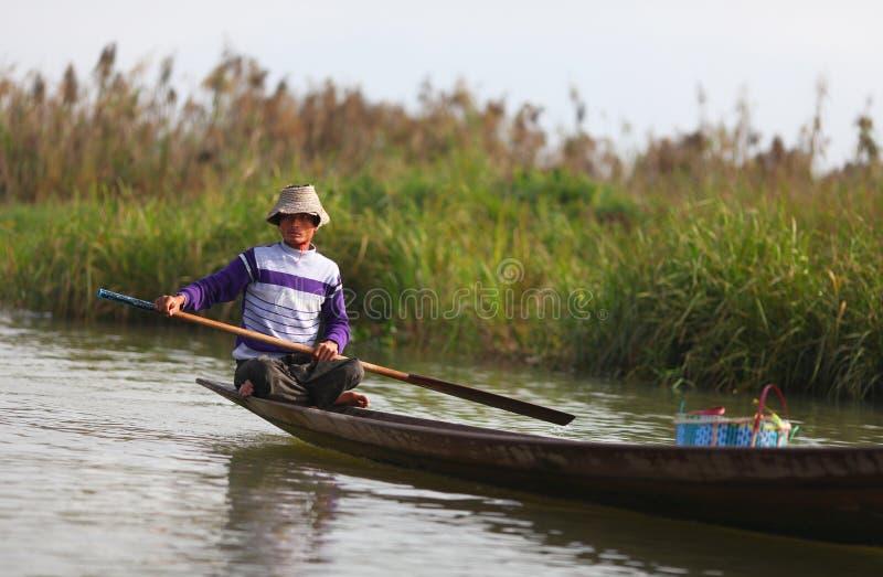 Pescador no lago Inle que enfileira sua canoa no wat foto de stock royalty free