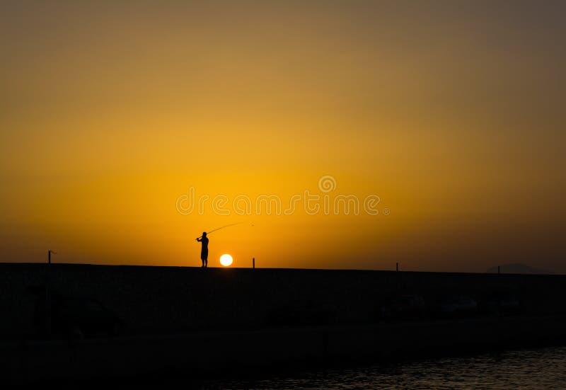 Pescador no por do sol no porto de Alimos em Atenas, Grécia fotografia de stock