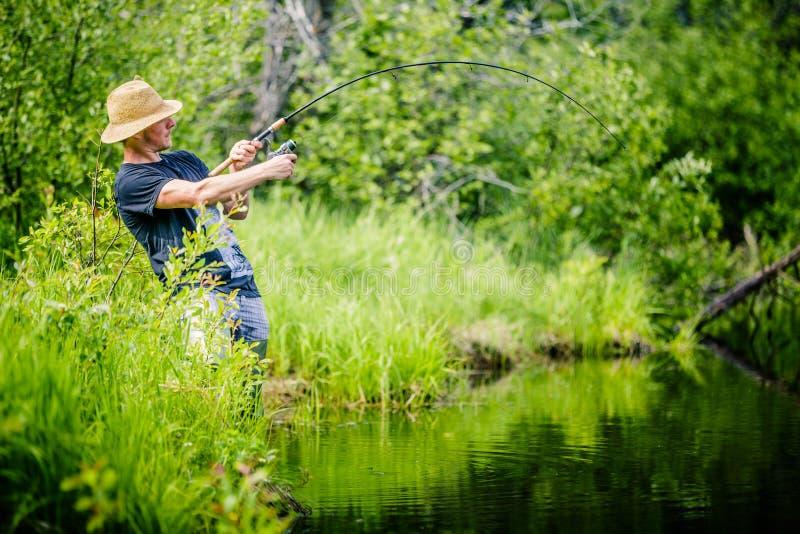 Pescador novo Catching um peixe grande imagens de stock royalty free