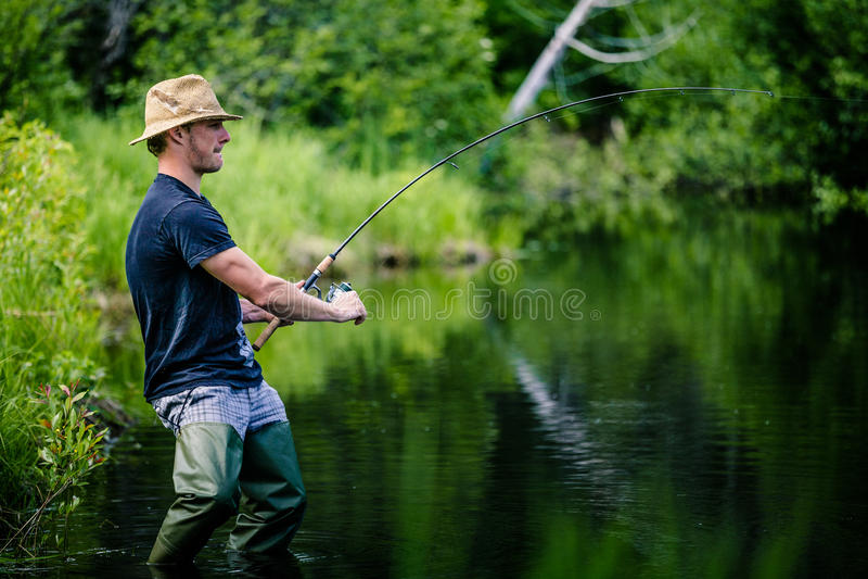Pescador novo Catching um peixe grande fotos de stock royalty free