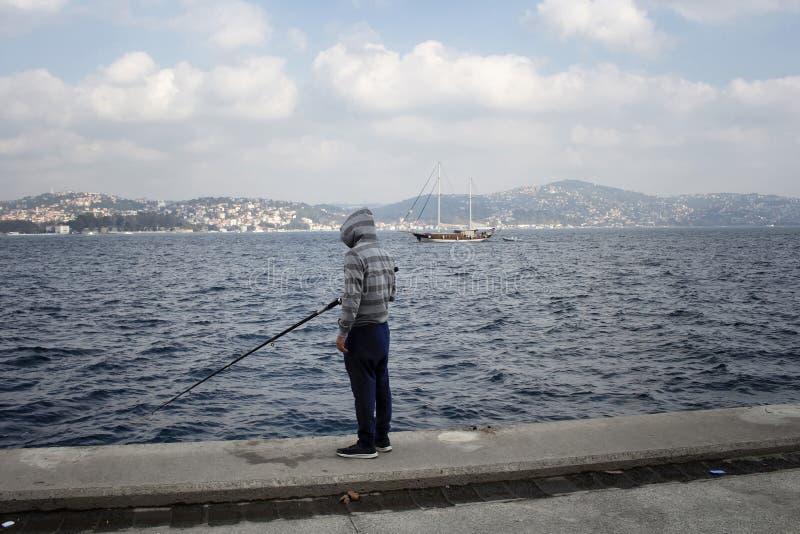 Pescador pelo passo de Bosphorus em Tarabya fotografia de stock