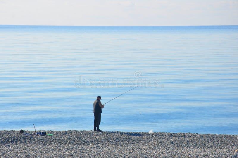 Pescador por el mar imagen de archivo