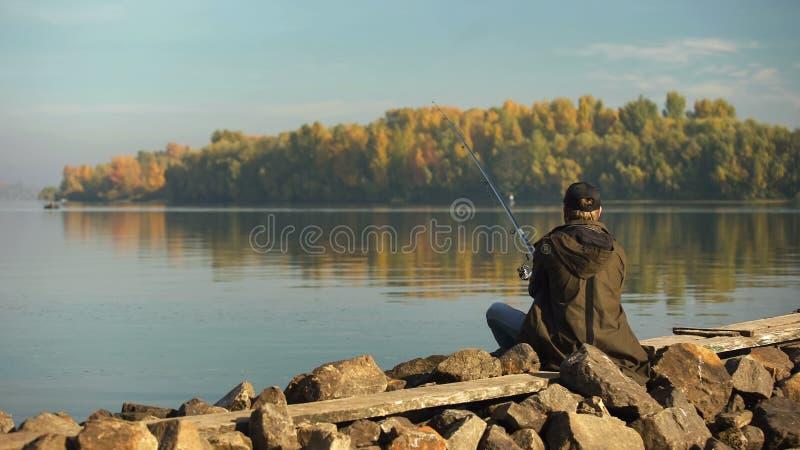 Pescador profissional que pesca no banco de rio, na haste e no equipamento, equipamento foto de stock royalty free