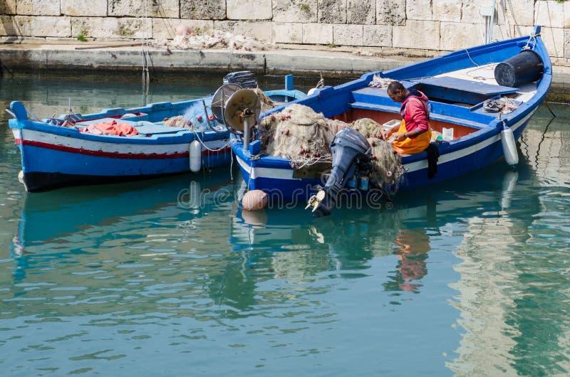 Pescador que arregla redes de pesca imagenes de archivo