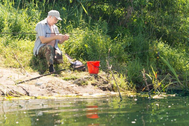 Pescador que atrai a seu gancho em uma costa do lago fotos de stock royalty free