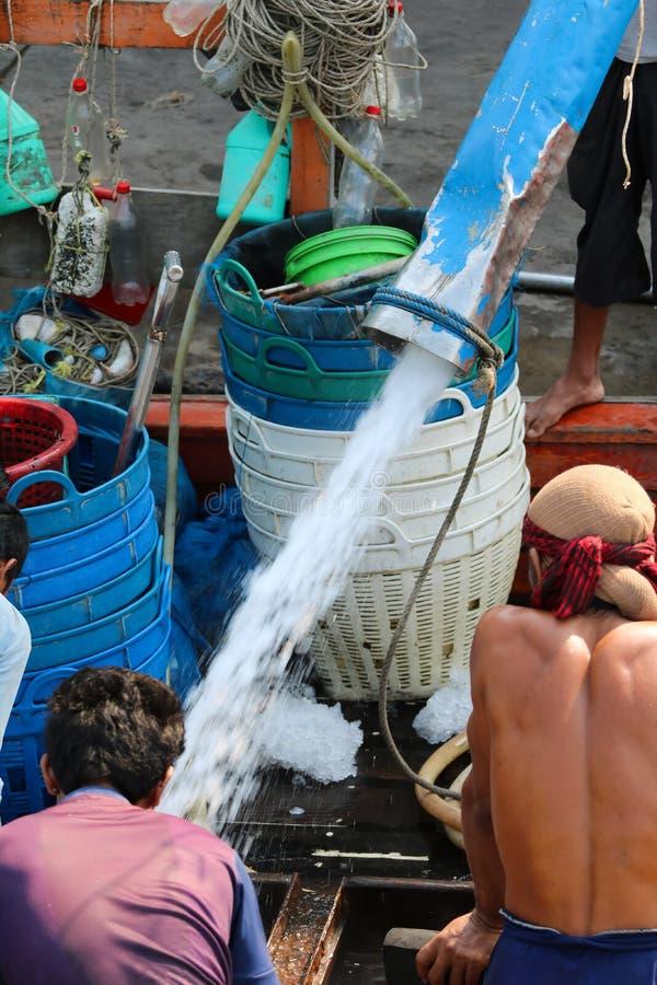 Pescador que espera descargando el hielo para los pescados congelados en el fishi fotos de archivo libres de regalías