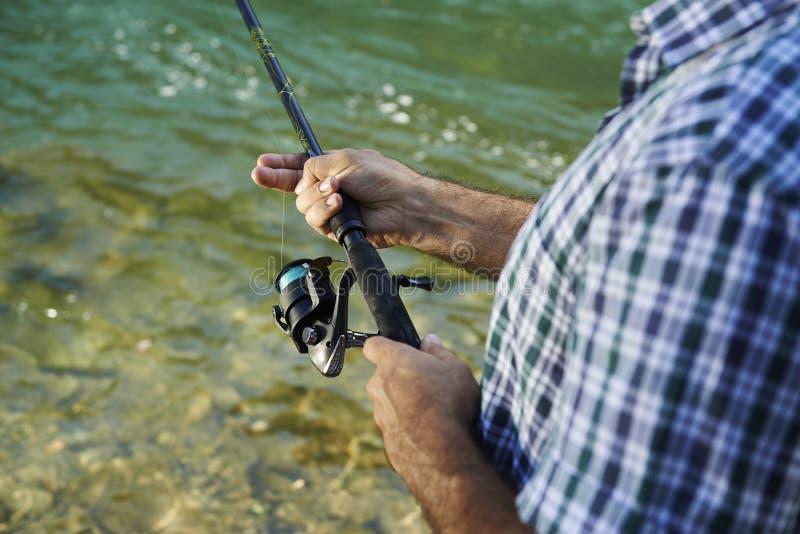 Pescador que está o rio próximo e que guarda a vara de pesca fotografia de stock royalty free