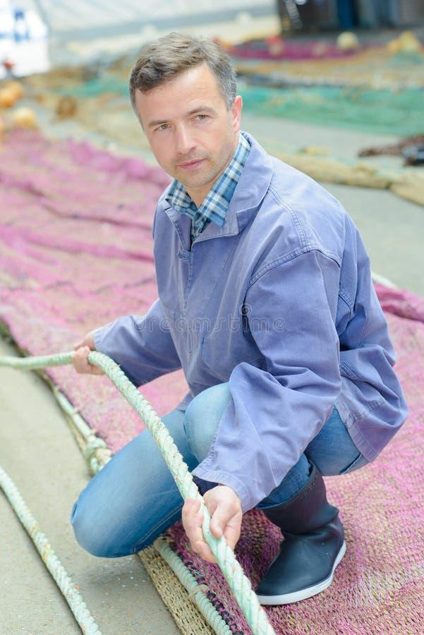 Pescador que lleva a cabo la red de la cuerda foto de archivo libre de regalías