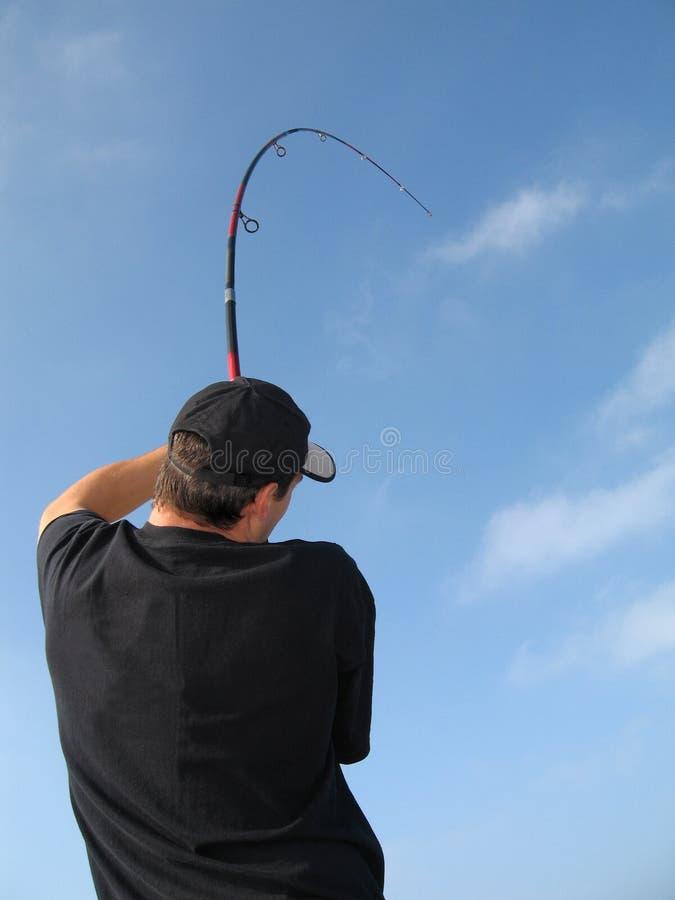 Pescador que luta um peixe imagem de stock royalty free