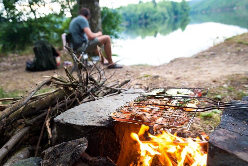 Pescador que prepara o jantar na fogueira, férias de acampamento da pesca do estilo de vida da aventura fotos de stock