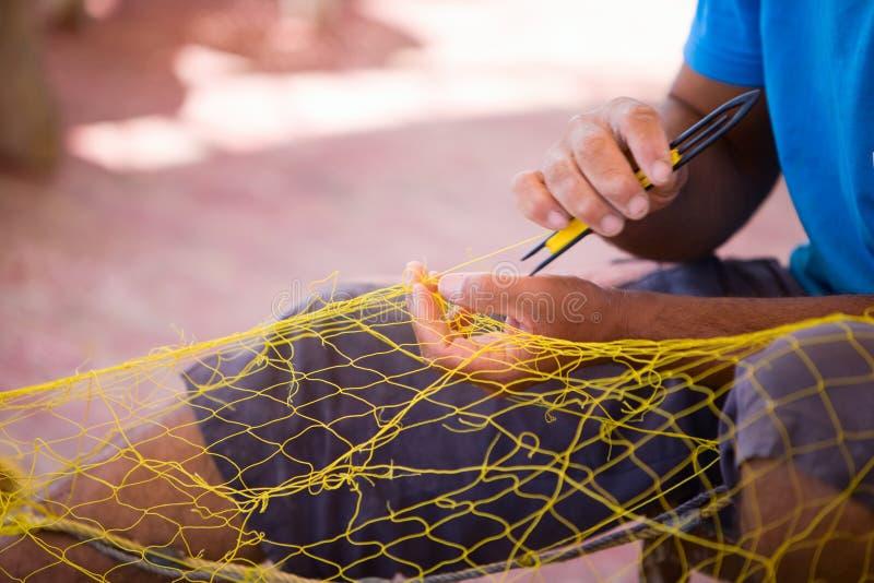 Pescador que repara a rede de pesca imagem de stock