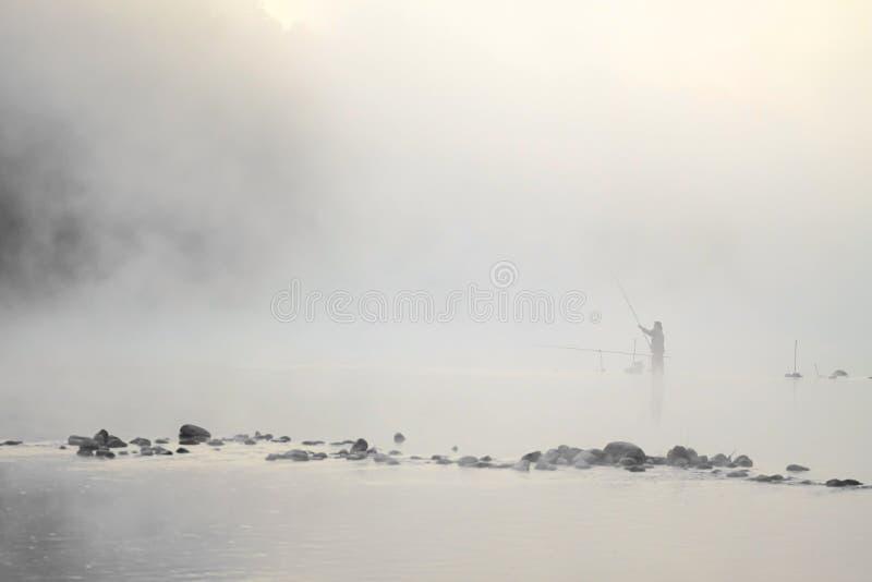 Pescador que se coloca en el agua foto de archivo libre de regalías
