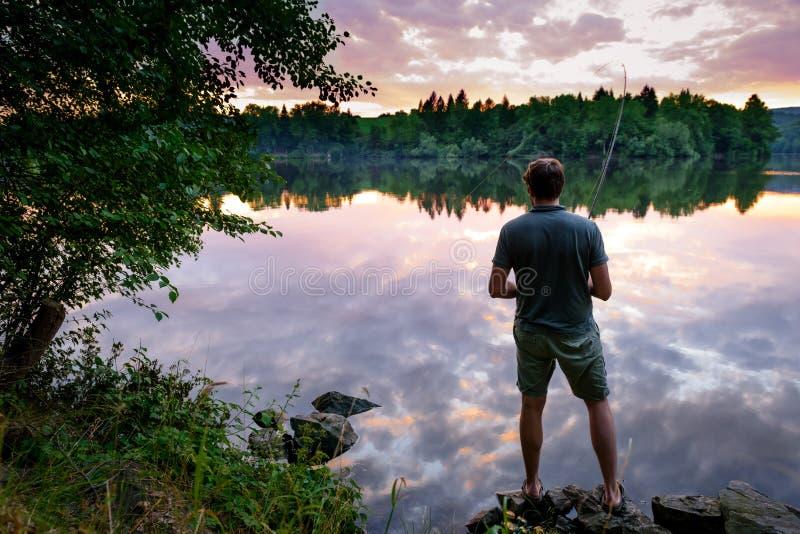 Pescador que se coloca en los bancos de Moldava en la puesta del sol hermosa, pescando concepto imagen de archivo