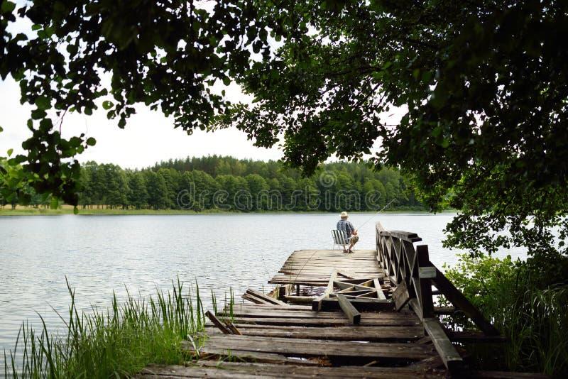 Pescador que se sienta en el embarcadero de madera en día de verano caliente y soleado Pesca del viejo hombre por un lago fotos de archivo libres de regalías