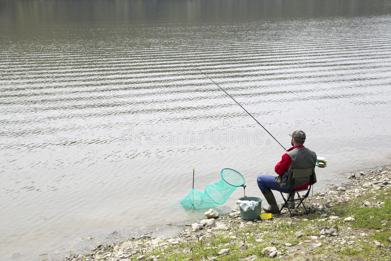 Pescador que se sienta en la costa del río y para los pescados pacientemente que esperan para tomar un cebo fotos de archivo libres de regalías