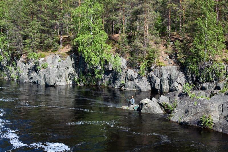 Pescador que se sienta en las rocas en el río imágenes de archivo libres de regalías