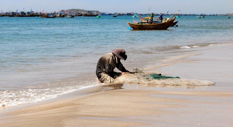 Pescador que senta-se em uma costa branca da praia da areia no sol da manhã que fixa sua rede fotos de stock royalty free