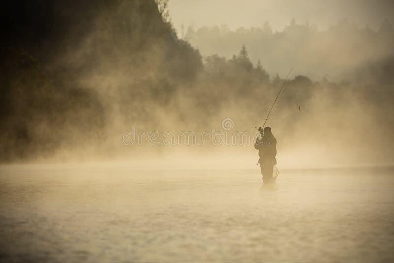 Pescador que sostiene la caña de pescar, colocándose en el río fotografía de archivo libre de regalías