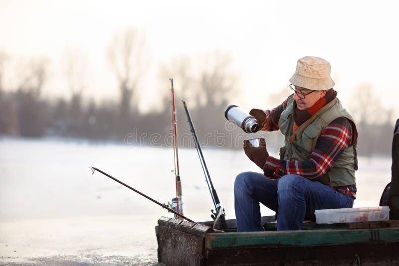 Pescador que toma o chá quente ao pescar peixes imagens de stock