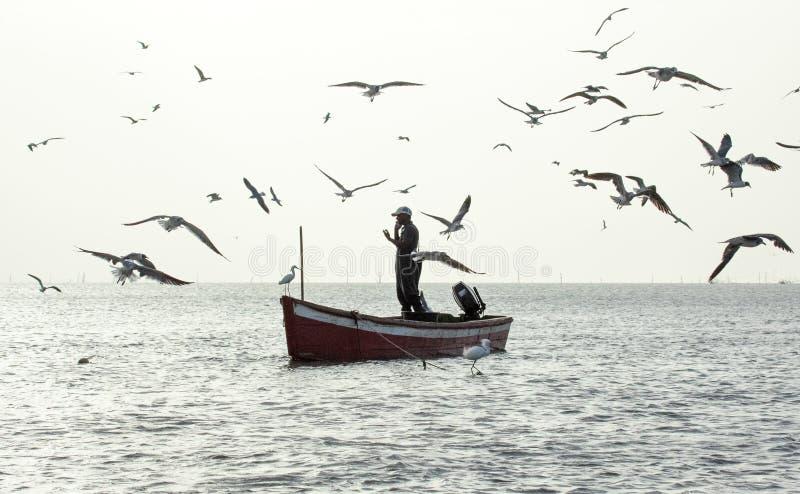 Pescador que usa su smartphone mientras que pesca fotos de archivo libres de regalías