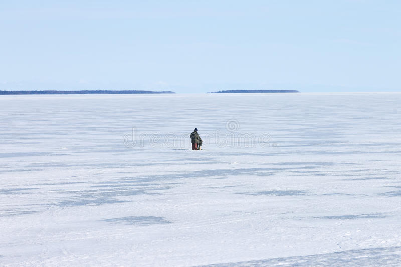 Pescador só no furo congelado do gelo da pesca de lago foto de stock