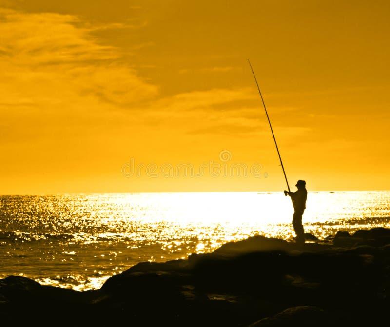 Pescador silueteado contra un s anaranjado foto de archivo