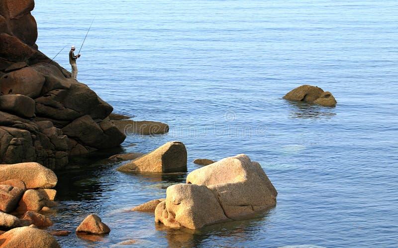 Pescador sobre las rocas de la costa rosada del granito en Bretagne foto de archivo libre de regalías