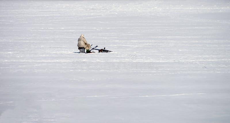 Pescador solo del hielo en el hielo de una charca congelada Visión desde la parte posterior imagen de archivo libre de regalías