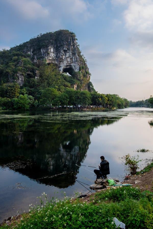 Pescador solo delante de la montaña del elefante foto de archivo