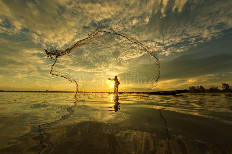 Pescador tailandés en el barco de madera que echa una red imágenes de archivo libres de regalías