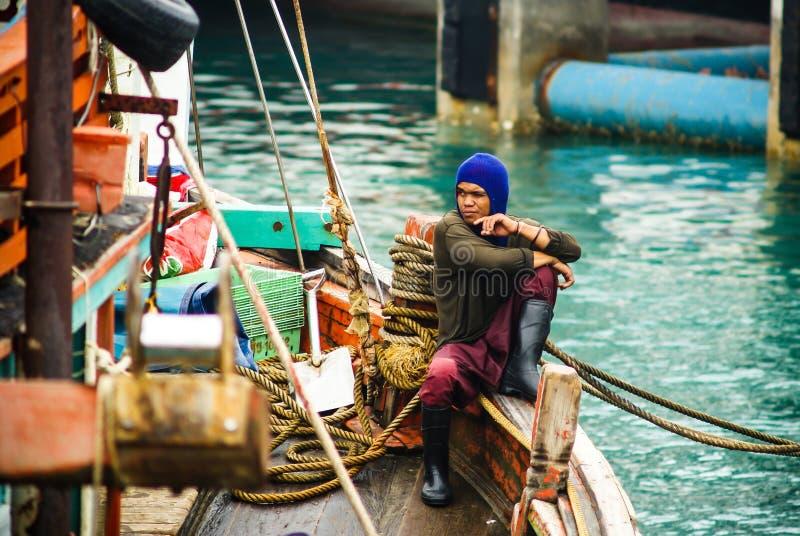 Pescador tailandês que senta-se no lado de um barco de pesca Ko Phangan tailândia 20 10 2011 foto de stock