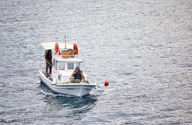 Pescador três turco masculino em uma navigação tradicional branca do barco de pesca sobre o mar em Gumusluk, Bodrum, Turquia foto de stock