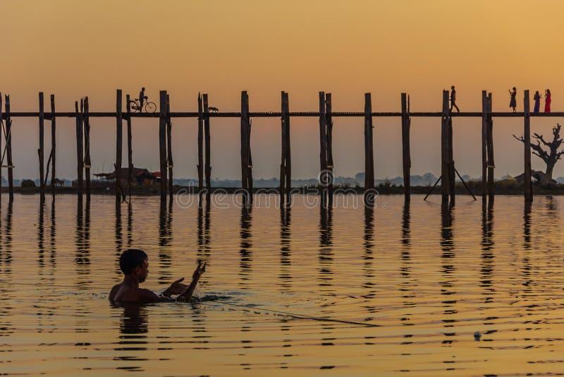 Pescador y puesta del sol en el puente del Teakwood de U Bein, Amarapura en M imágenes de archivo libres de regalías