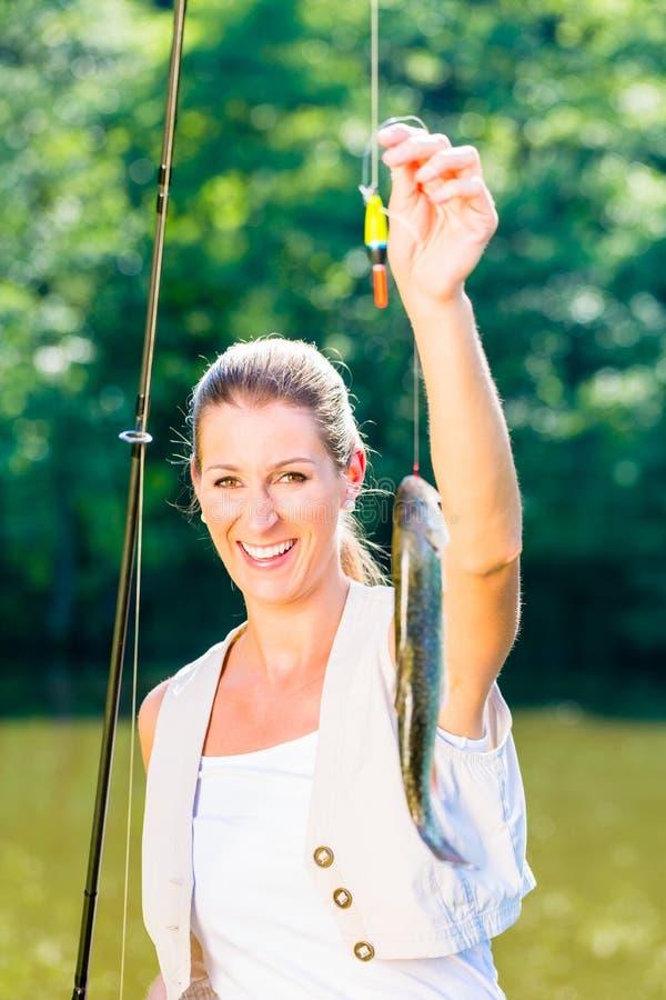 Pescadora do esporte que mostra sua captura imagem de stock royalty free