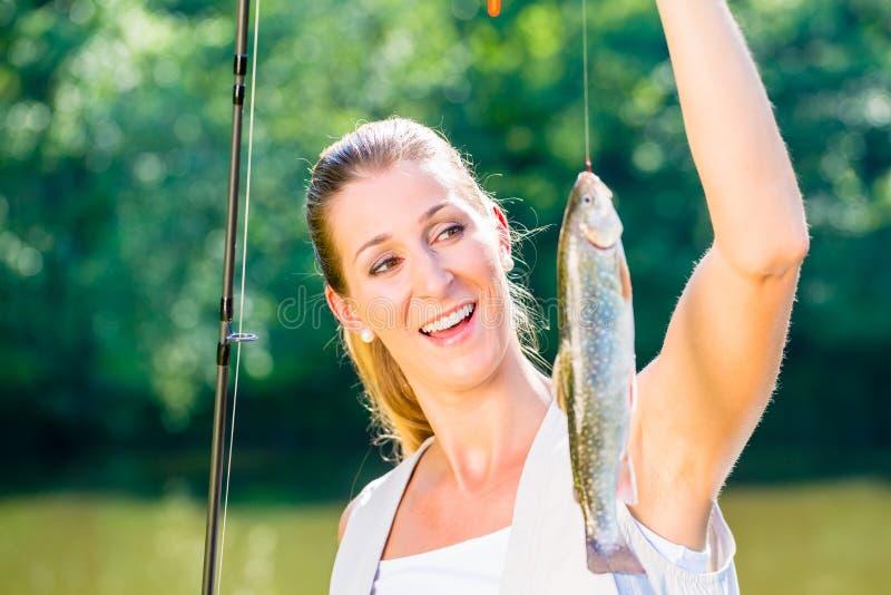 Pescadora do esporte que mostra sua captura foto de stock