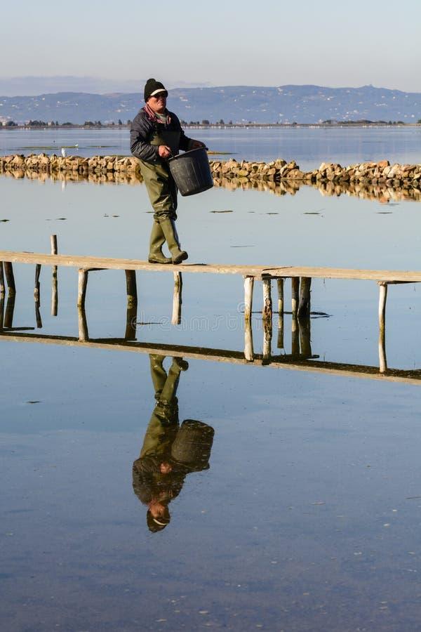 Pescadores con sus barcos antiguos, ca?da en el amanecer Oeste del sur de Cerde?a imagen de archivo