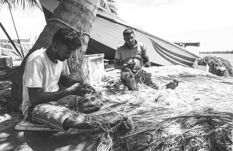 Pescadores consertando rede de pesca na praia imagem de stock