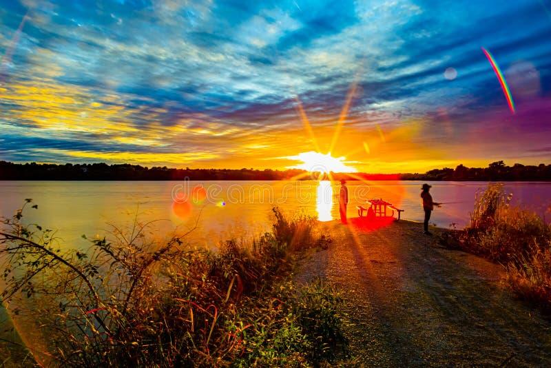 Pescadores desportivos em Sunset no outono antecipado com lindos paraquedas sobre o lago Ed Zorinsky Omaha Nebraska imagem de stock royalty free