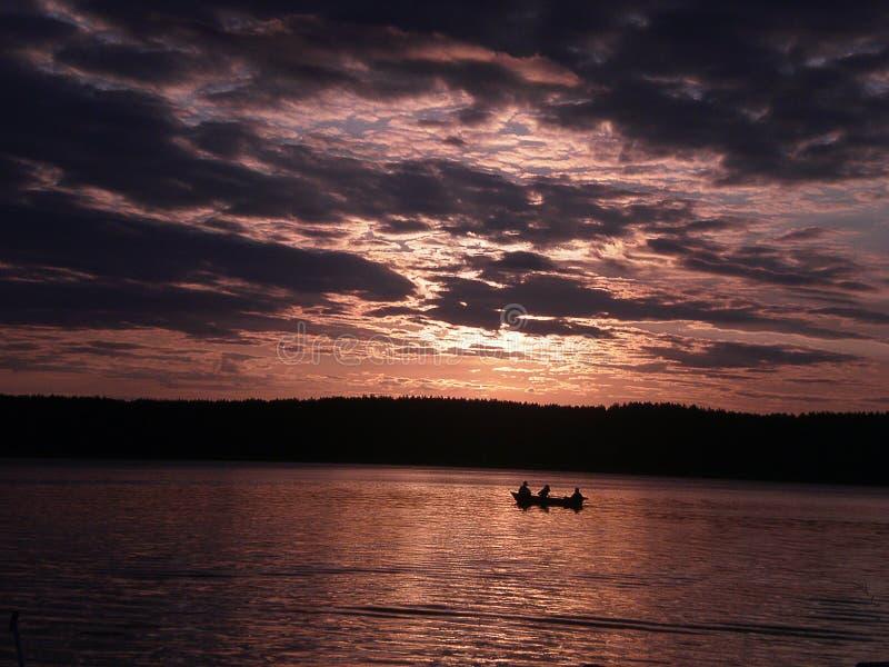 Pescadores em um barco no por do sol imagem de stock royalty free