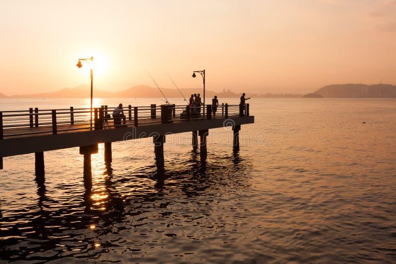 Pescadores en el embarcadero de Santos durante la puesta del sol del verano imagen de archivo